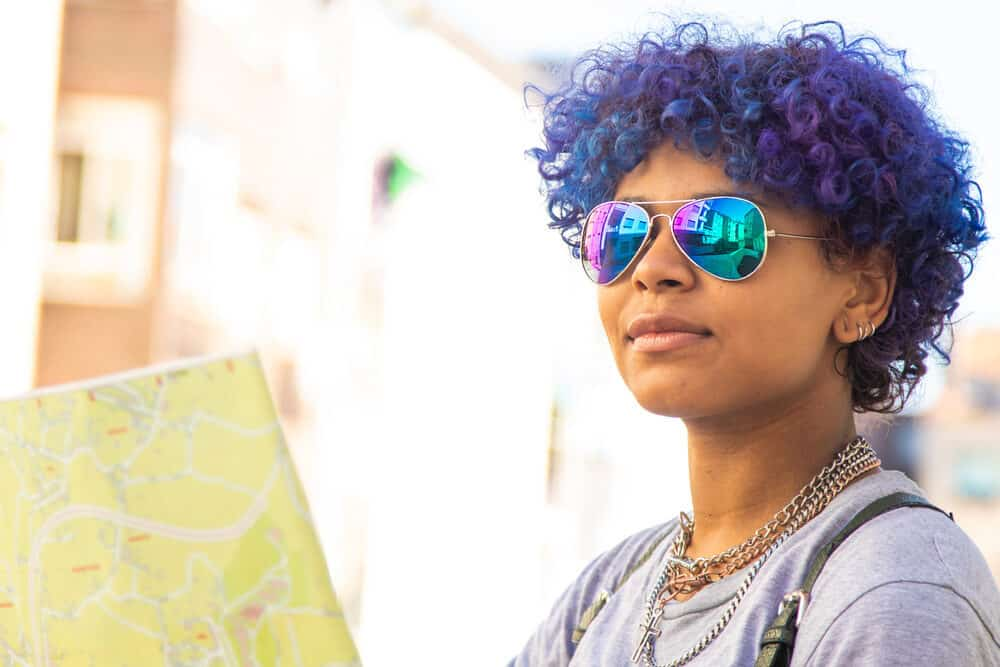 Female wearing rainbow shades, purple-blue hair, earrings, and natural lipstick color.