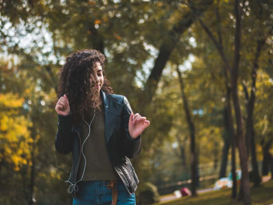 Mixed-raced female dancing outside while listening to music on earphones while wearing a black jacket, green sweater, and blue jeans.