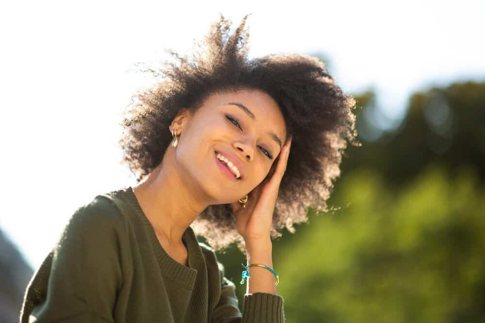 Young American female standing outdoors smiling on a sunny day.