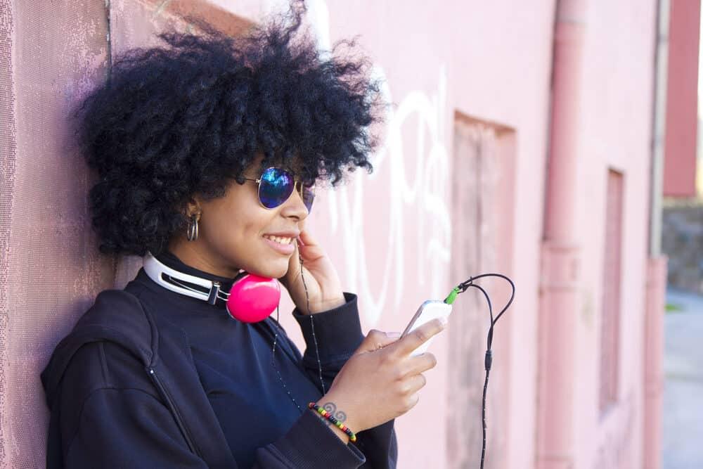 Pretty black female with tight curls wearing a black shirt, dark jacket, and hoop earrings.