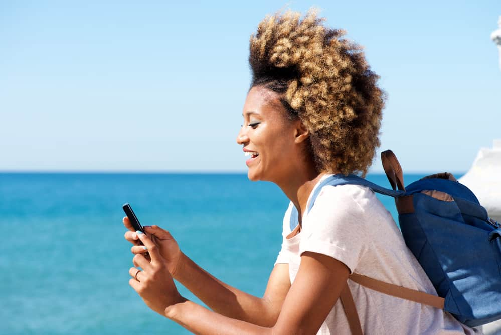 African American women with braided type 4c hair strands using a mobile phone on a boat.