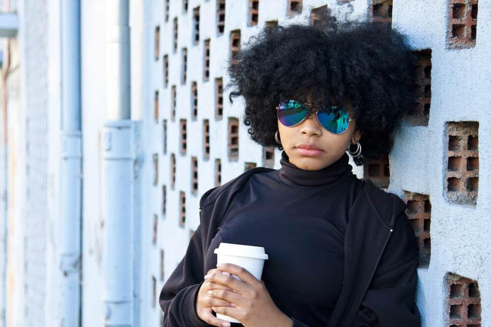 Lady standing outside drinking coffee wearing a mock turtleneck and hoop earrings.