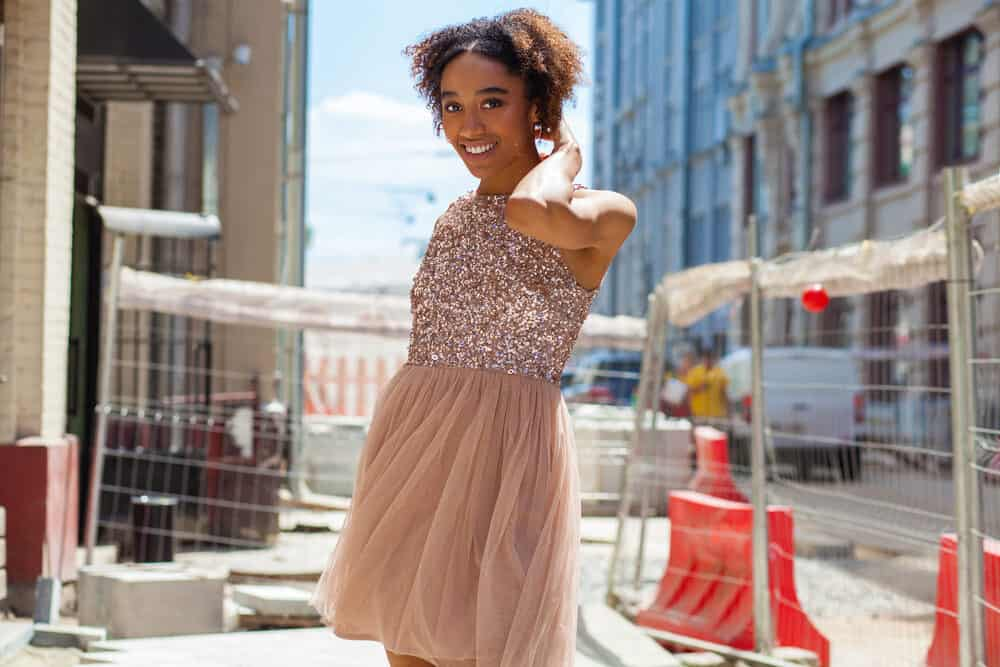 Cute black girl with a big smile wearing a pink dress.
