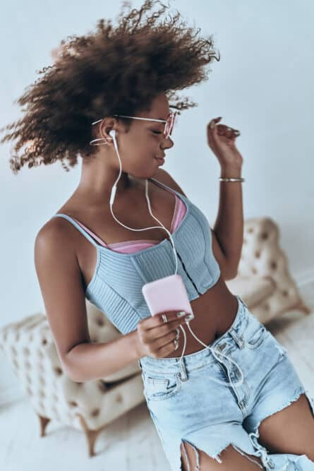 Black girl dancing and shaking her hair in the wind while wearing casual clothes and listening to music.