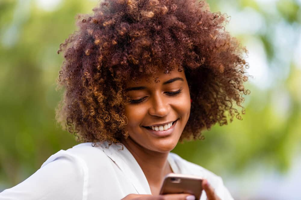 Pretty black girls with natural hair reading an article on her mobile phone while sitting on a bench at the park