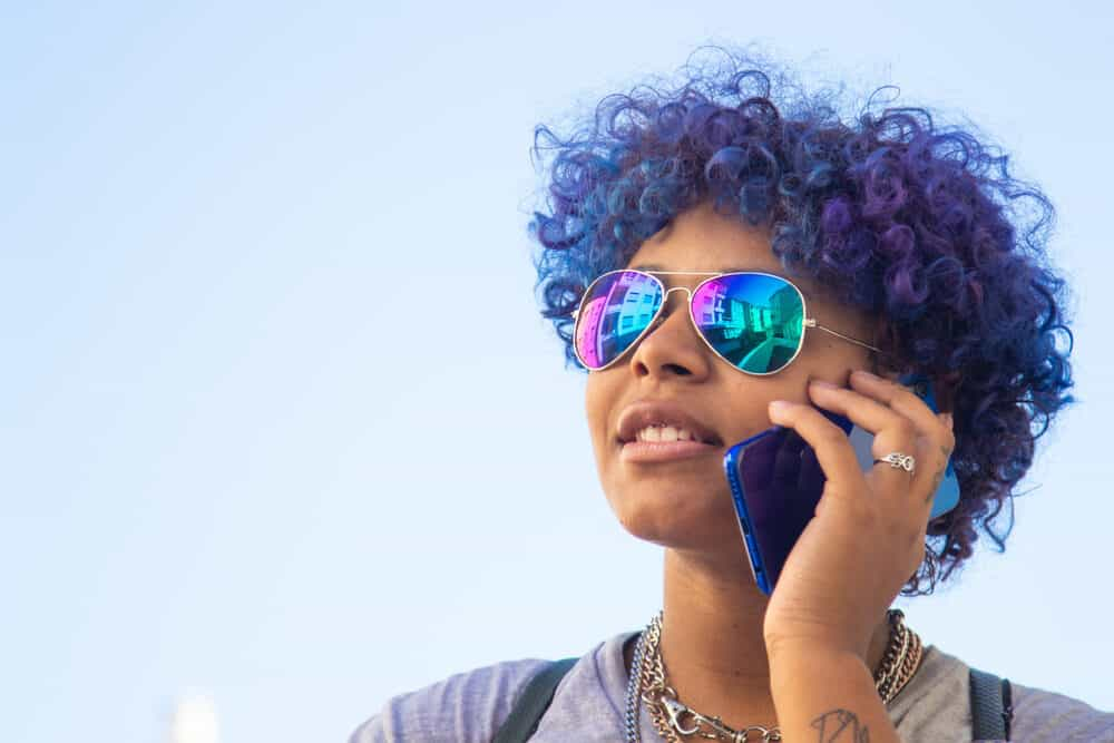 Mixed-race Latin black girl outside talking on a mobile phone with curly hair strands.