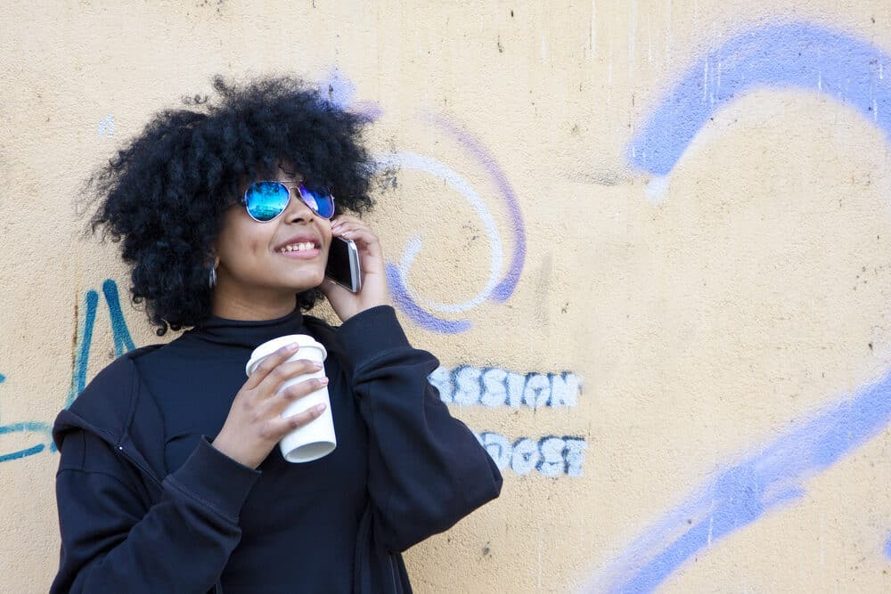Black women with curly hair wearing shades while drinking a cup of coffee outside.