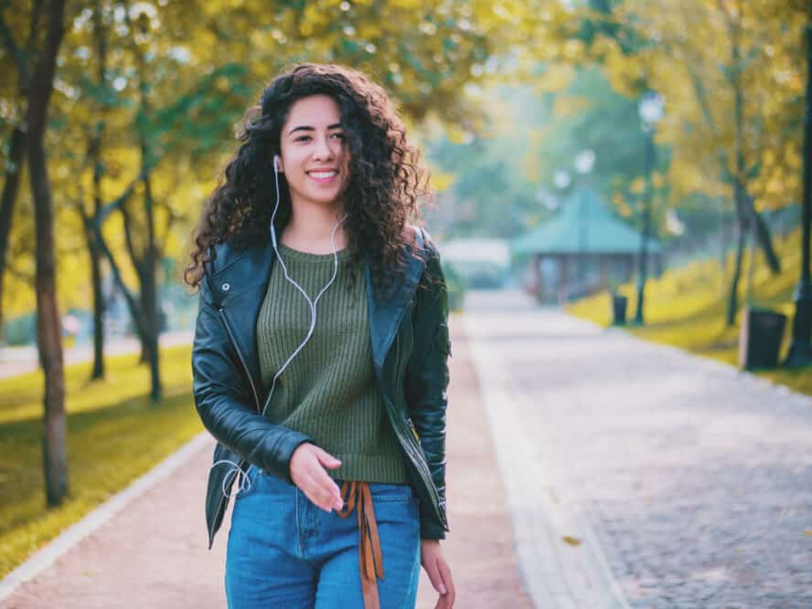 Smiling mixed race female with wavy hair wearing a black leather jacket during the fall season while listening to songs on Apple earphones.
