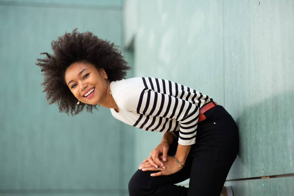 Young black women with 4b hair strands after using a tea tree scalp treatment standing against a wall wearing red lipstick, earrings, a blue and white sweater, red belt, and black jeans.