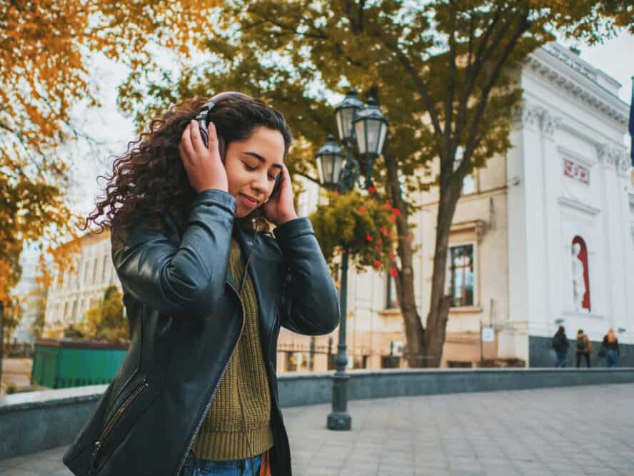 Latin women with naturally curly hair listening to music on Bose headphones wearing a green shirt, blue jeans, and a black leather jacket.