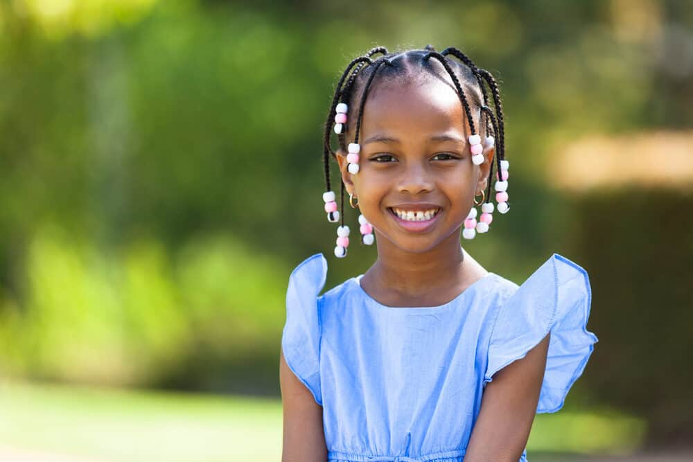 Learn how to put beads in your hair like this little girl with pink and white hair beads.