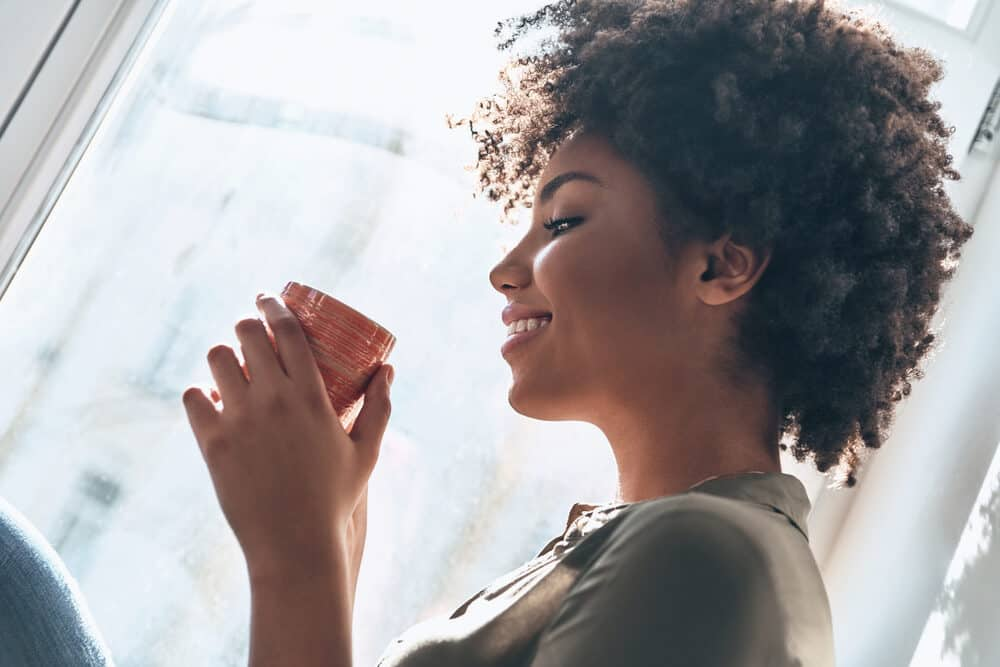 Women with 4c hair type having a cup of coffee during an early summer morning
