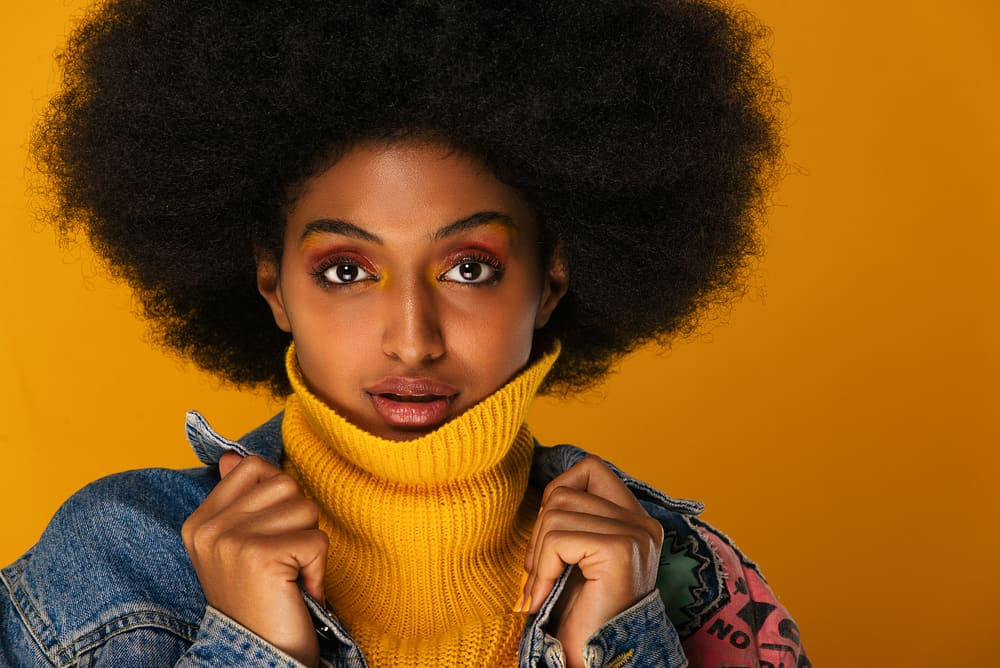 Light-skinned female with 4c natural curls wearing a blue jean jacket and yellow sweater