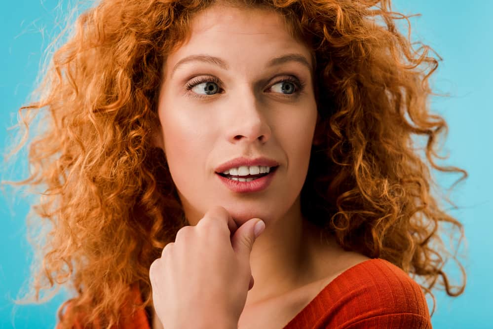 Caucasian adult female with mc1r gene as a natural red hair and light skin tone wearing a red shirt.