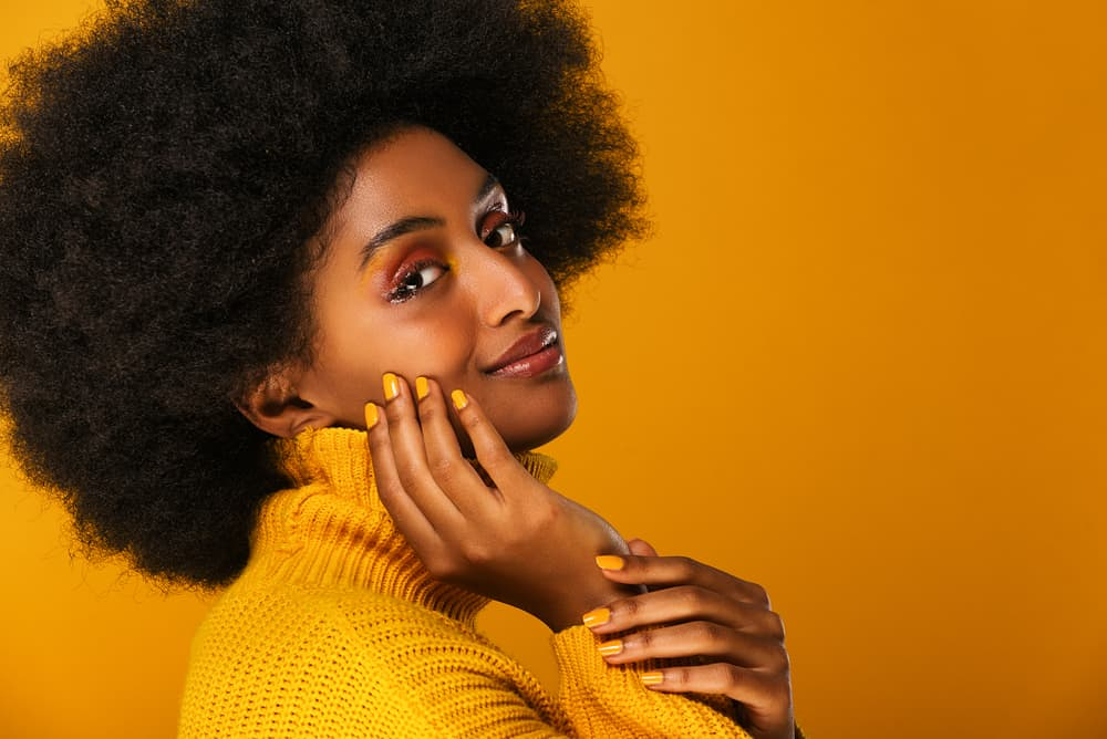 Young black female wearing a yellow sweater and fingernails with naturally curly hair with a fresh henna mixture