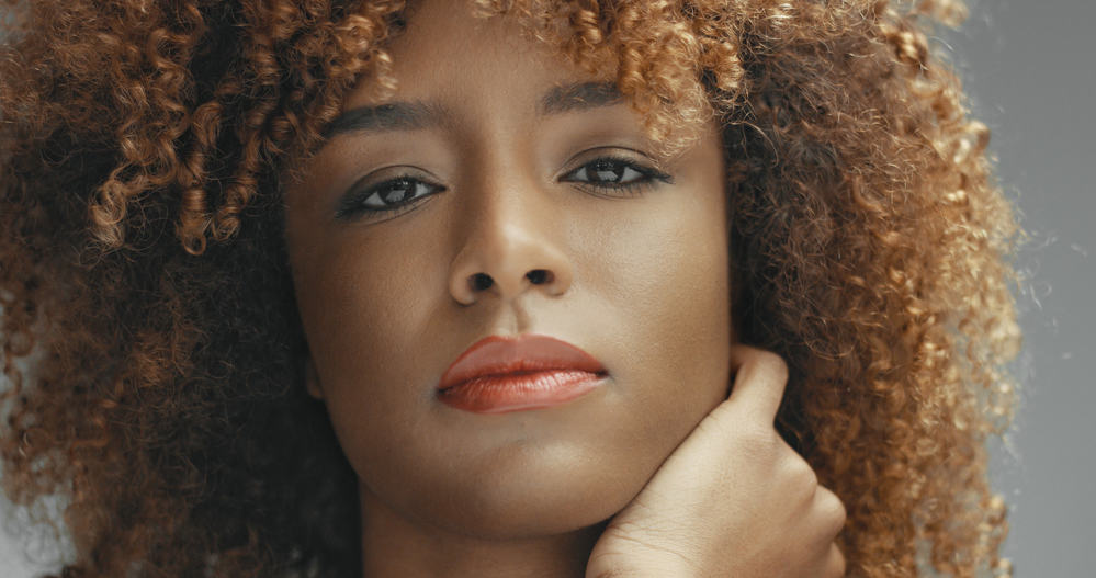Beautiful black lady with blonde and brown curls looking directly into the camera
