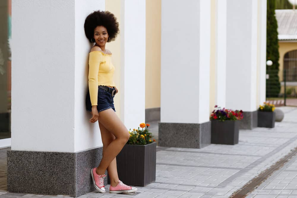 Black adult female wearing a light yellow shirt, blue shorts, and pink converse sneakers