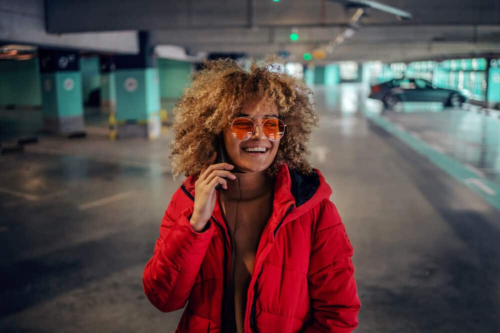 A young woman with curly hair, carrying a phone to her ear as she stands in the underground garage.