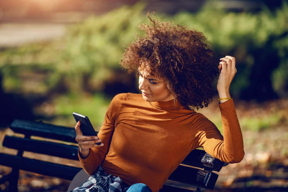 A young woman with a mixed-race in New York City is sitting on a bench using her phone.