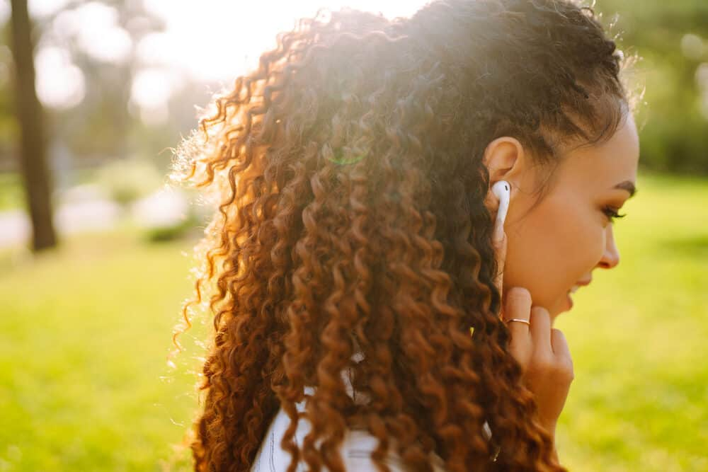 African American girl with curly hair follicles wearing Apple air pods
