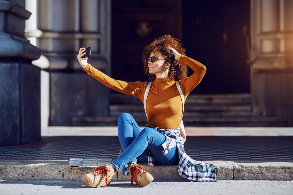 A young woman with curly hair takes a selfie while sitting on the ground outside.
