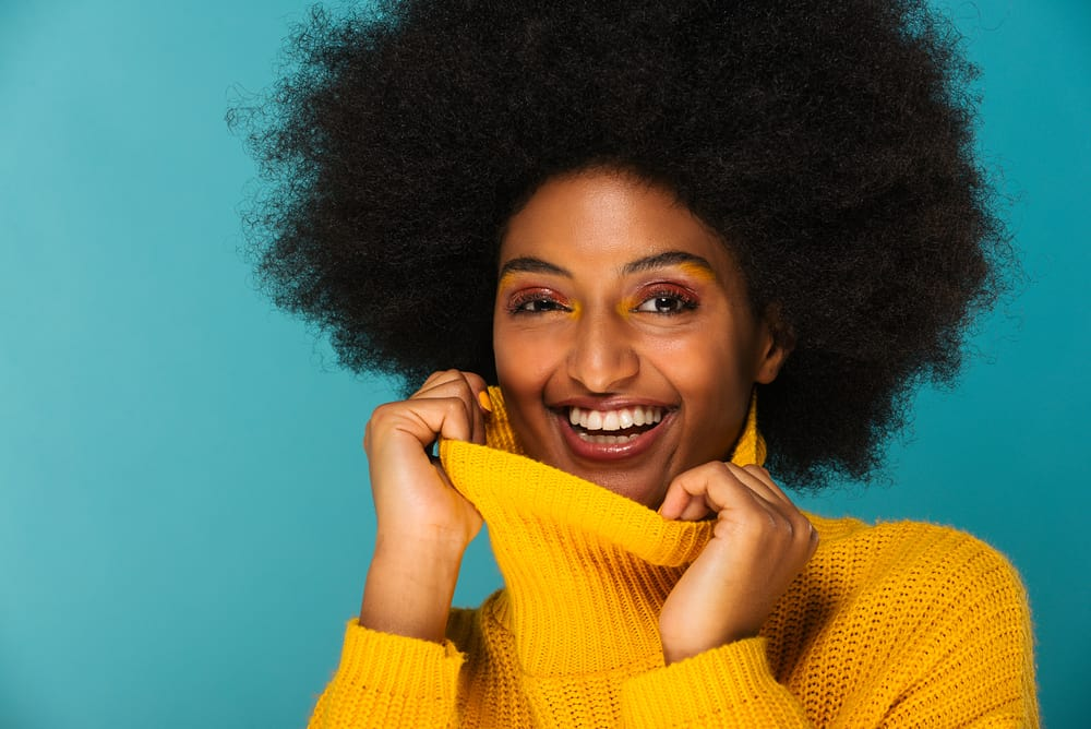 Cute black girl with 4c natural highlights wearing a yellow sweater