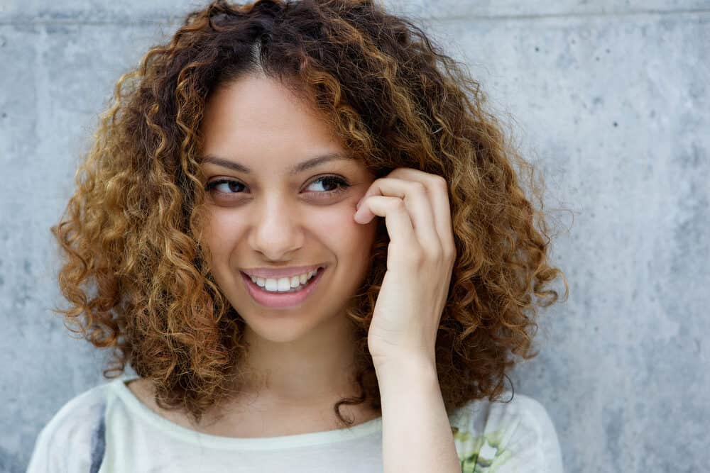 Light-skinned black girl with curly bleached hair wearing a big smile while touching her face
