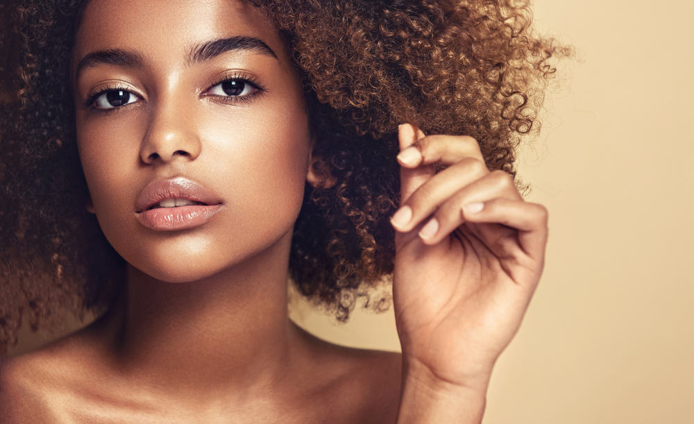 Cute black female showing off brown curls and pink lipstick.