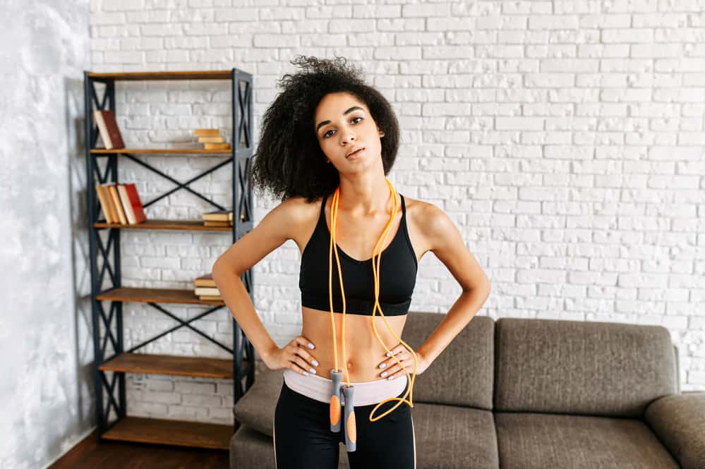 A beautiful woman with curly hair getting ready to jump rope at home.