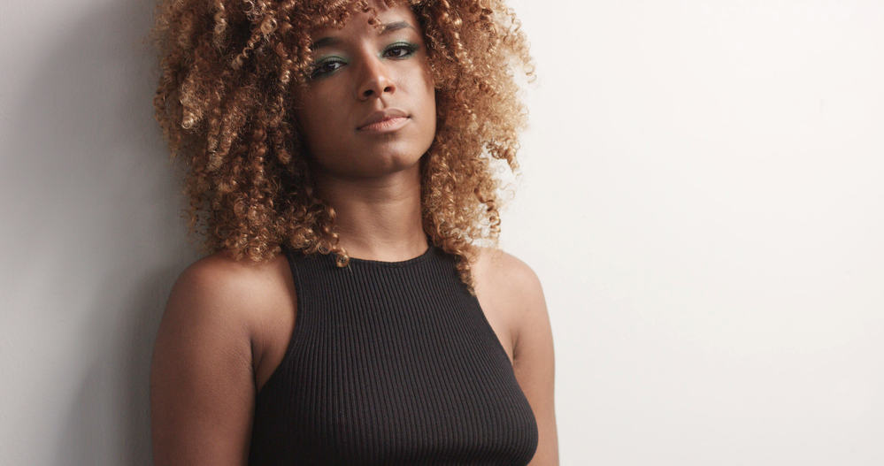 Black female with ombre curly hair and a black dress
