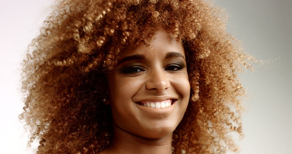 Black girl with a big smile wearing neutral  foundation makeup on her face