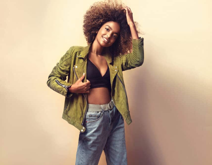 African American women wearing a green jacket, black shirt, blue jeans, and naturally curly brown hair strands.