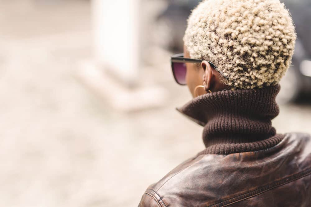 Black woman with a blonde curly afro hairstyle wearing a brown leather coat, hoop earrings, and glasses
