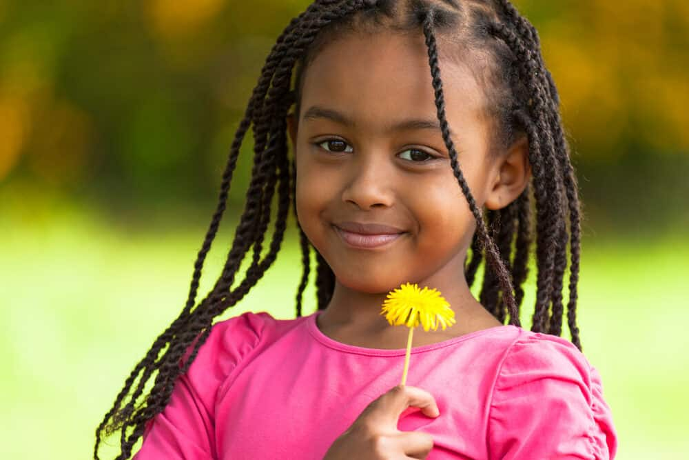 Cute African American girl holding a dandelion flower showing off her natural beauty with the perfect hairstyle