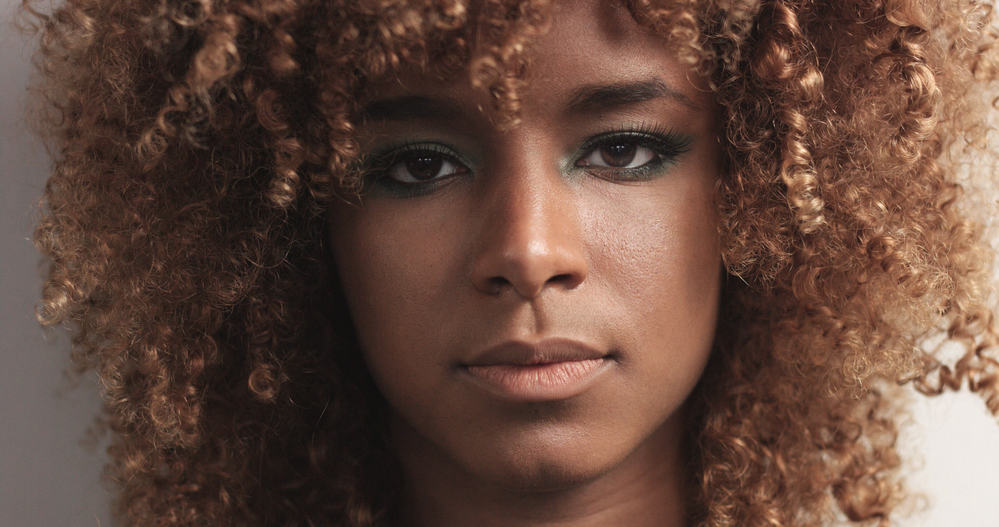 Close-up of light-skinned black girl with a curly texture and blue eyeshadow to compliment her style