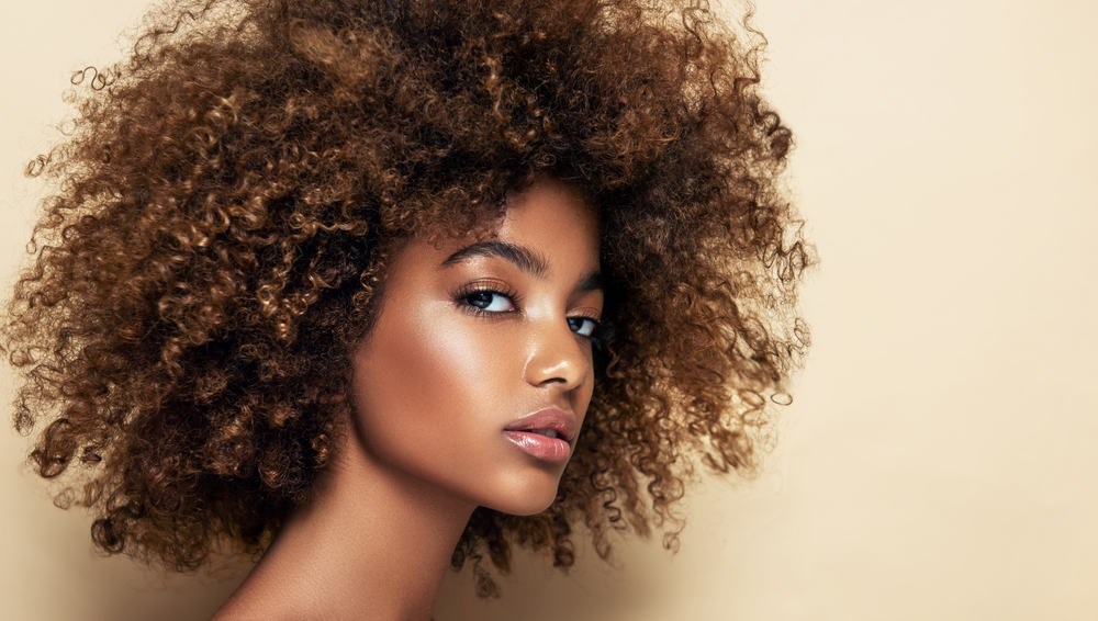 Cute black female with brown curls, freshly arched eyebrows, and pink lipstick.