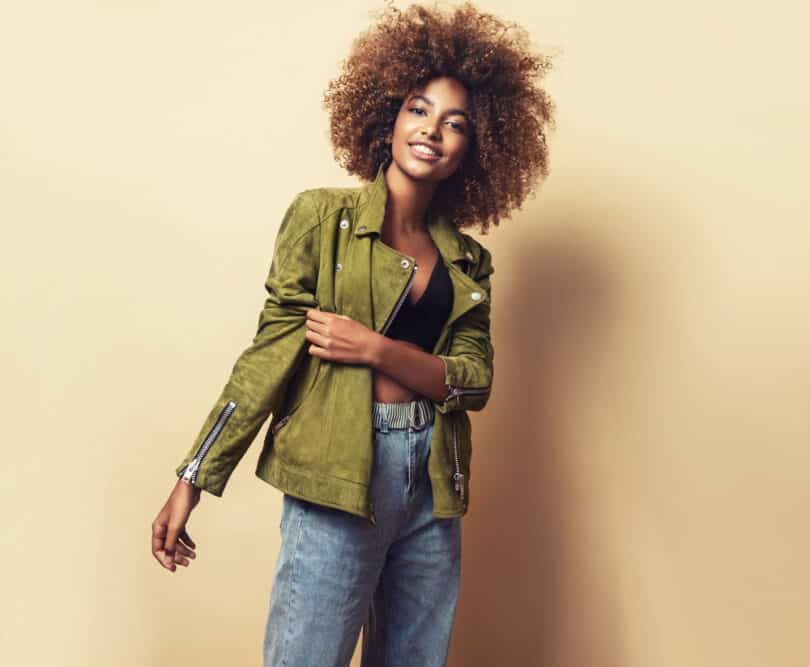 African American woman smiling while wearing a green winter jacket, blue pants, and hair that is naturally curly.