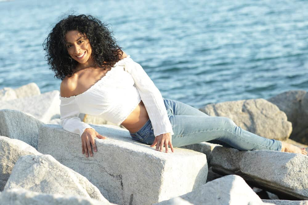 Black woman laying on rocks on the edge of the beach