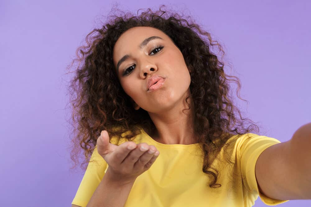 Young black girl blowing a kiss to the camera while taking a selfie