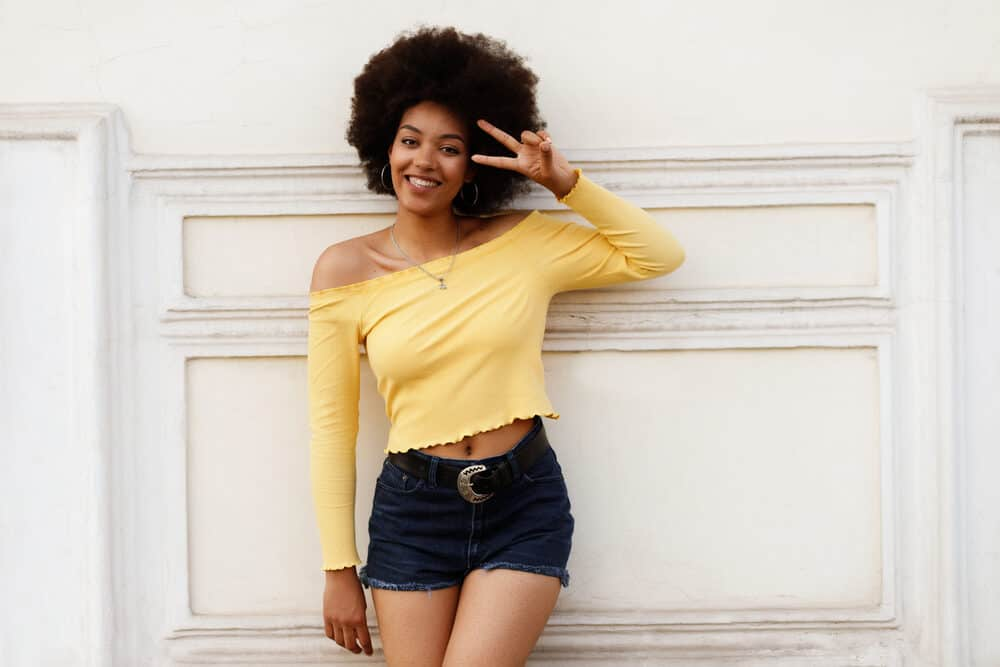 Cute African American women with virgin hair wearing a brassy yellow shirt and blue jean shorts