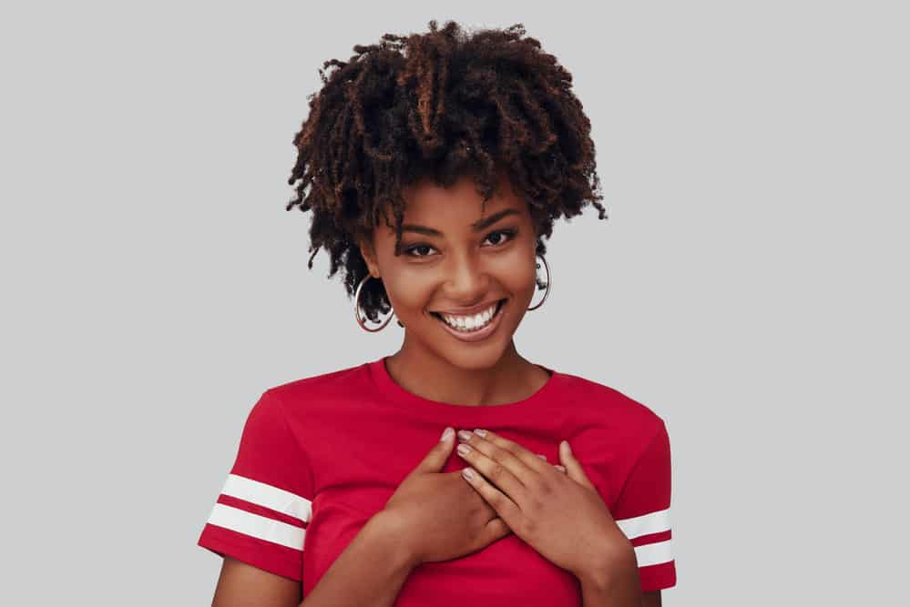 Black girl wondering how to detangle matted hair while wearing a red shirt with white stripes on the sleeves