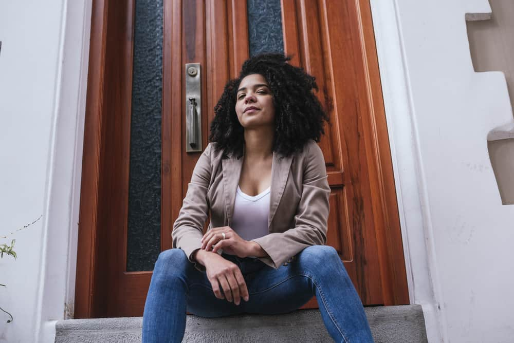Light skinned female sitting outside wearing blue jeans, a white shirt, brown jacket, and curly natural hair