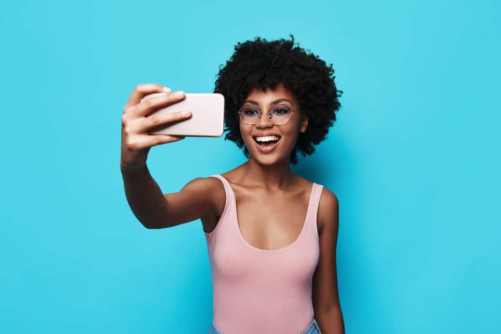 Lady wearing a pink shirt while taking a selfie with her mobile phone