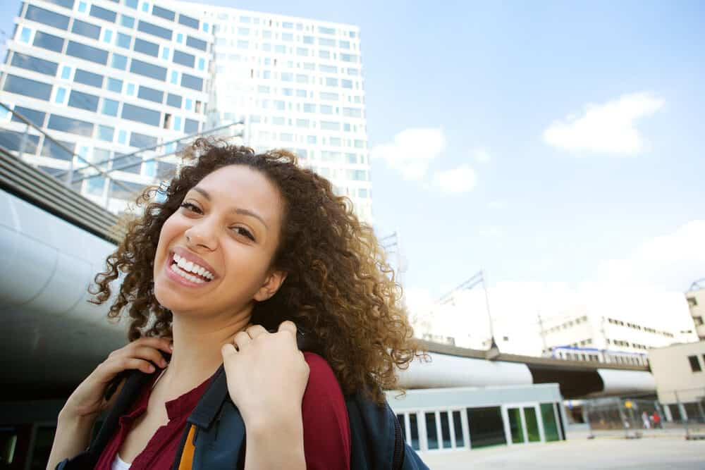 Smiling lady with natural hair standing outside wearing a backpack on a sunny day