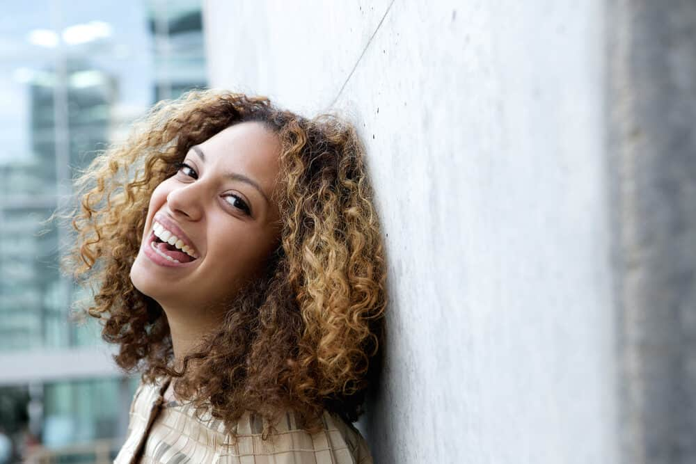 Light skin complexion mixed-race girl laughing while looking directly into the camera