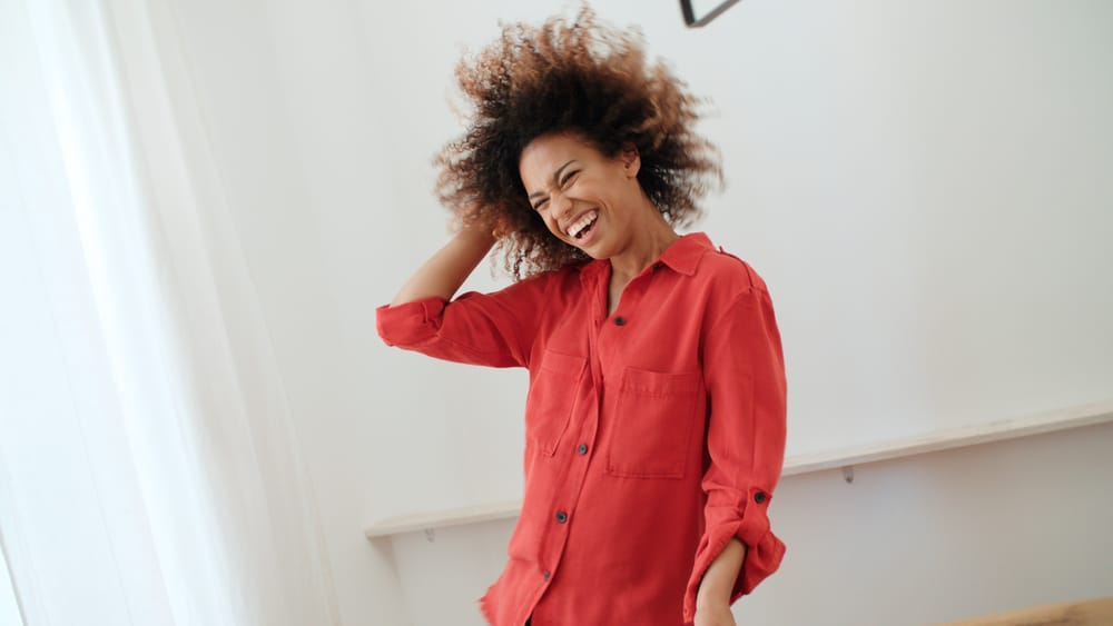 Black female ready to leave the house after a shower wearing a red dress shirt