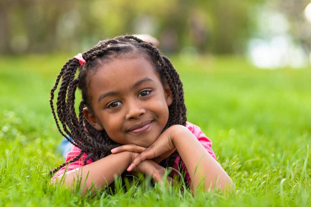 Young girl with an adorable hairstyle with braids all around while lying down on the grass