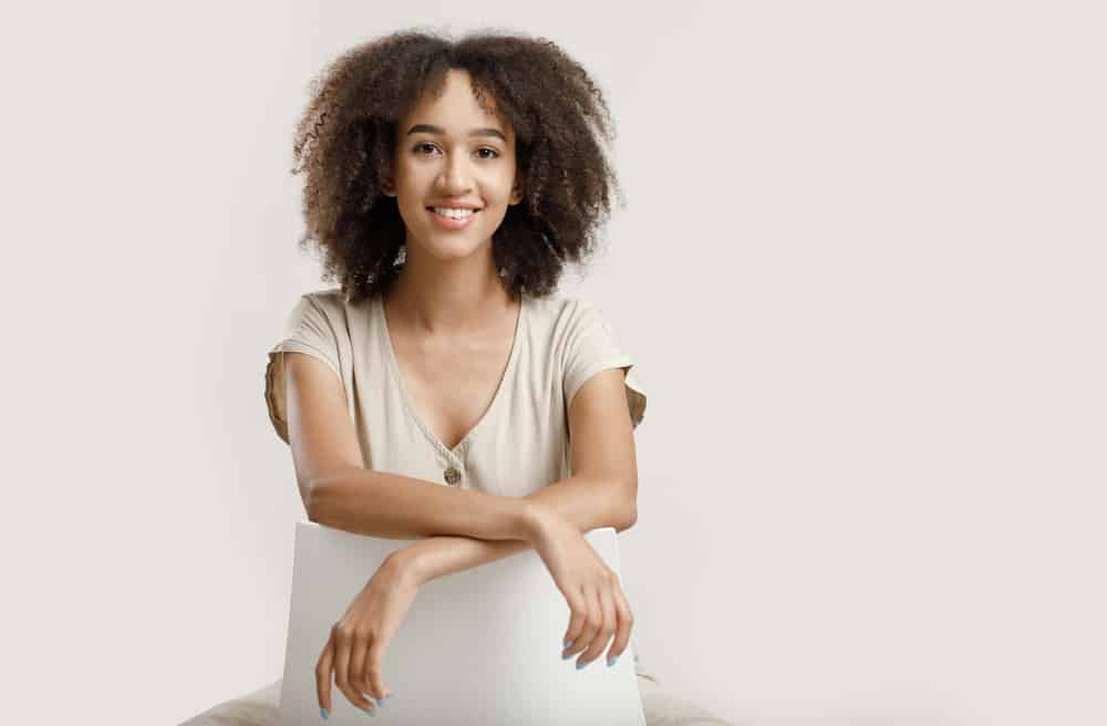 Young African American blogger with naturally curly hair sitting on a white chair