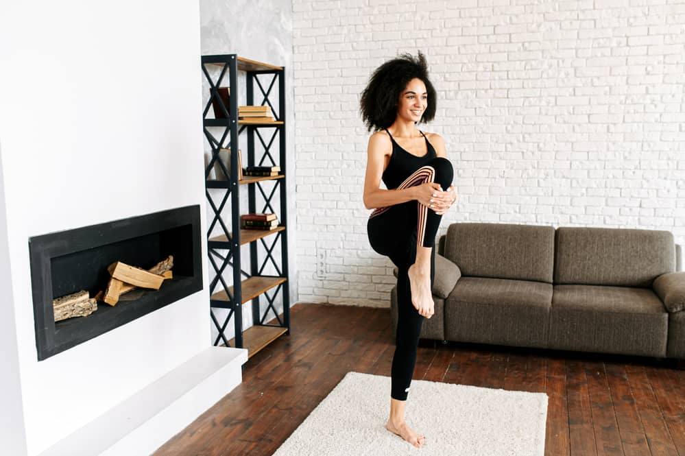An African-American girl with 4b natural hair in sportswear is stretching her legs in a cozy living room.