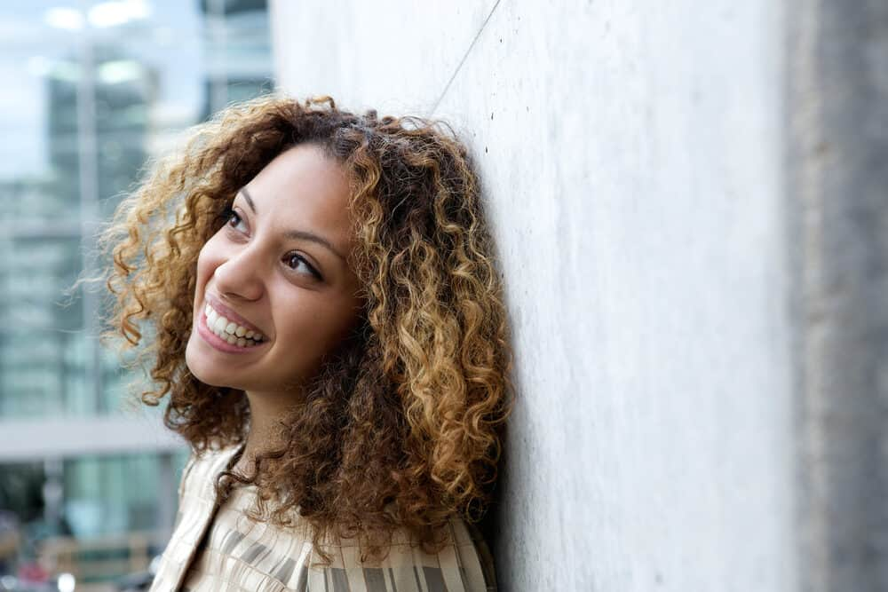 African American female wearing light and dark brown ombre hair follicles looking into the distance
